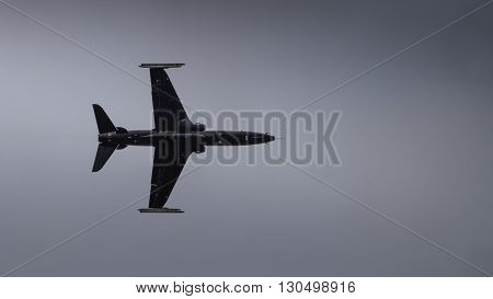Silhouette of a black jet fighter in flight