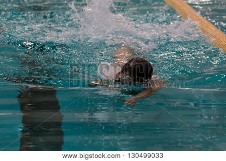 Swimmer In The Pool. Freestyle Swimming. Low Key, Dark Background, Spot Lighting, And Rich Old Maste