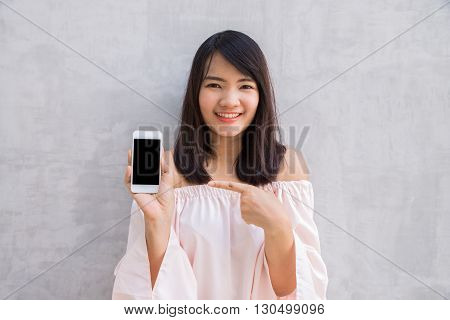 Smiling woman showing a blank smartphone screen standing on concrete wall.