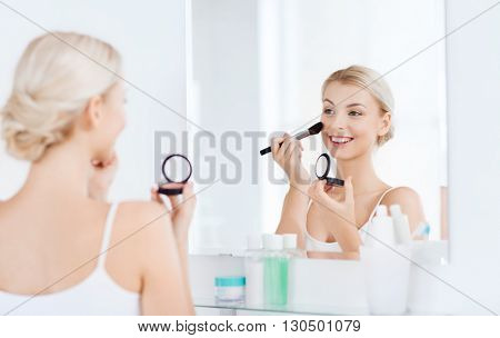 beauty, make up, cosmetics, morning and people concept - smiling young woman applying blush with makeup brush and looking to mirror at home bathroom