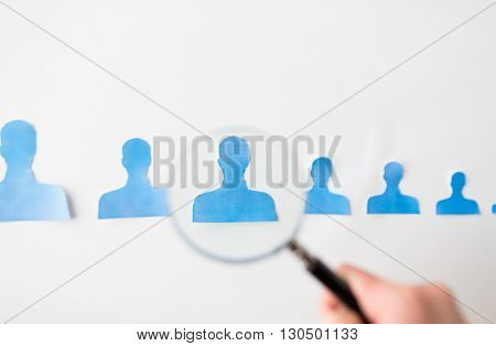 business, employment, population, career and hiring concept - close up of paper people shapes and hand with magnifying glass on white board