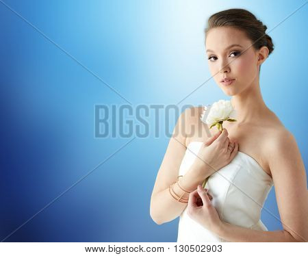 beauty, jewelry, people and luxury concept - beautiful asian woman or bride in white dress with peony flower, golden ring and bracelet over blue background