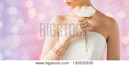 glamour, beauty, jewelry and luxury concept - close up of beautiful woman with golden ring and bracelet holding flower over pink holidays lights background
