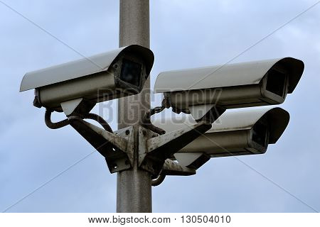 video surveillance cameras on a column against the background of the blue sky