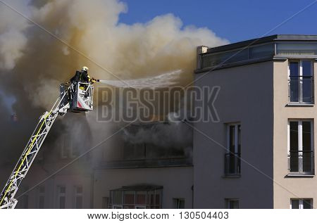 Two firefighters on a crane quench a burning house