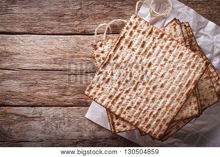 Jewish Kosher Matzah Closeup On Paper On A Table. Horizontal Top View