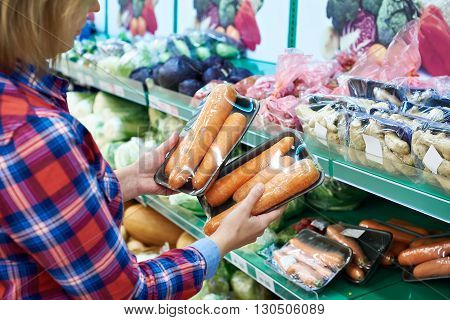 Woman Selects Carrot In Store