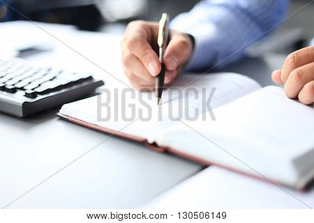 Businessman makes a note in his notebook