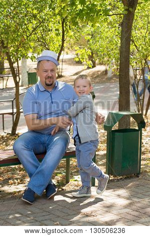 the father with the son sit in park on a bench and have fun