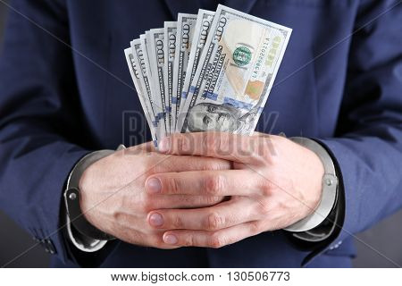 Man in handcuffs counting dollar banknotes, close up