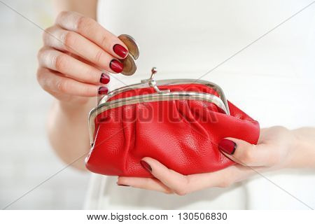 Young woman getting euro coins from purse