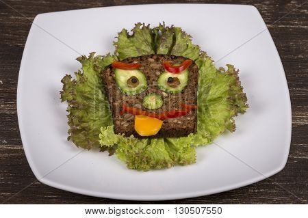 Fun food for kids face on bread made from lettuce tomato cucumber and pepper. Close up