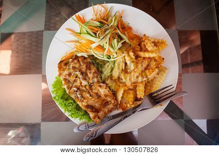 Fresh bbq barracuda fish fillet.Traditional khmer cambodian cuisine sreved with chips and salad.