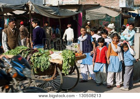 LUCKNOW, INDIA - DEC 19, 2012: Unidentified children have fun on the crowed indian street at the sunny day on December 19, 2012 in Lucknow India. Lucknow in Uttar Pradesh state has population of 4,588,455