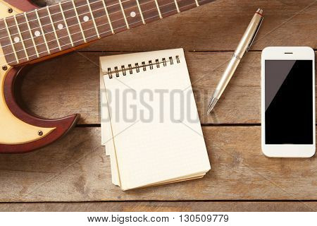 Notebook and smartphone on wooden background