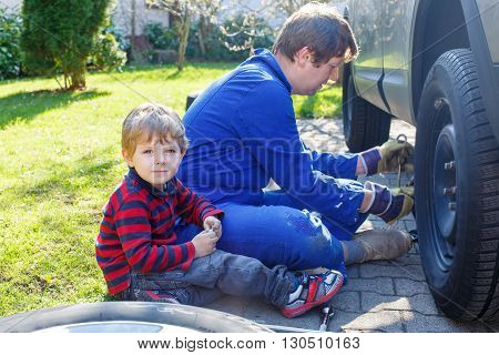 Funny little kid boy and his father changing wheels on car with pneumatic wrench. Man in uniform teaching his son working with tools.
