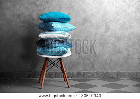 Few pillows on chair against blue wall background