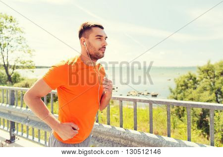 fitness, sport, people, technology and healthy lifestyle concept - happy man with earphones running outdoors