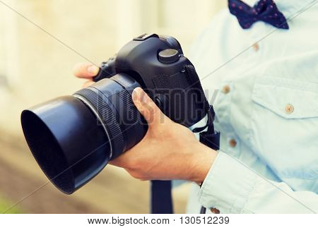 people, photography, technology, leisure and lifestyle - close up of male photographer with digital camera on city street