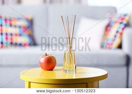 Handmade reed freshener with red apple on yellow table in living room, close up