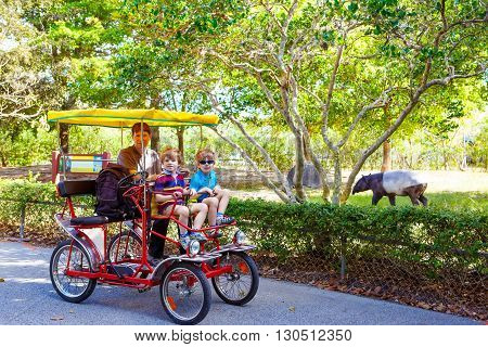 Yound dad and two little kid boys biking on bicycle in zoo. Family with active leisure and watching animals. Father and sons having fun together. Miami zoo, Florida.