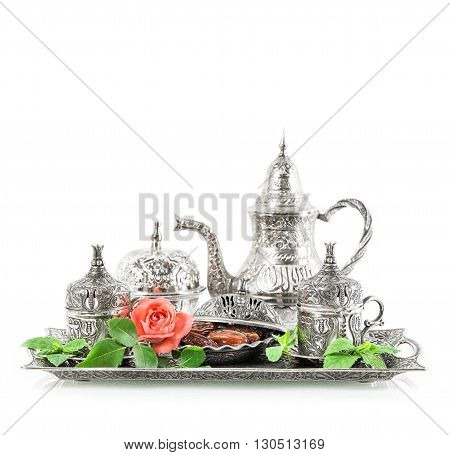 Holidays tea table setting with mint leaves and rose flower. Eid mubarak. Oriental hospitality concept