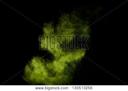 Light green powder explosion on black background. Colored powder cloud. Colorful dust explode. Paint Holi.