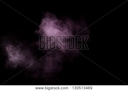 Purple powder explosion on black background. Colored powder cloud. Colorful dust explode. Paint Holi.