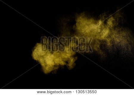 Yellow powder explosion on black background. Colored powder cloud. Colorful dust explode. Paint Holi.