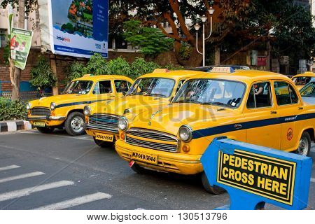 KOLKATA, INDIA - JANUARY 19, 2013: Vintage yellow taxi cabs stopped at a pedestrian crossing on January 19, 2013 in India. Kolkata has a density of 814.80 vehicles per km road length