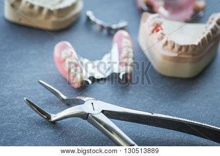 Artificial Replacement Teeth With Forceps On A Dark Table