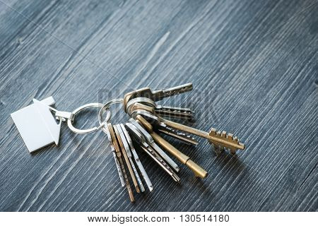 Bunch Of Keys With House Shaped Key Ring On A Wooden Table