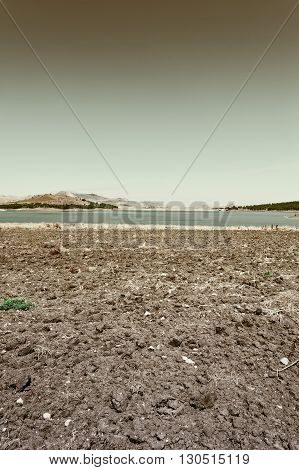 Plowed Shore of the Lake Lago di Ogliastro on the Background of the Mount Etna in Sicily Retro Image Filtered Style