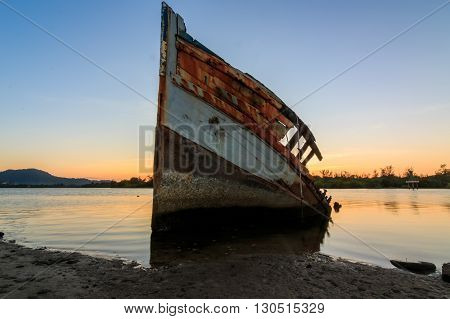 Abandoned Ship during sunset moment at Sabah Borneo Malaysia Image has grain or blurry or noise and soft focus when view at full resolution. (Shallow DOF, slight motion blur)