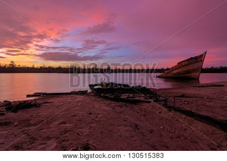 Old wreck on the shore in Borneo , Old fishing boat with the sunset momment