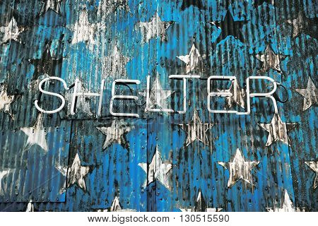 Word shelter made up of neon tubes on the background of a stylized image fragment of an American flag on a rusty fence