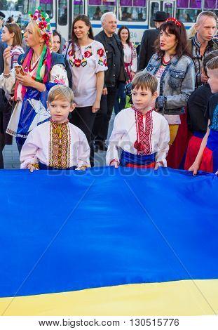Zaporizhia/Ukraine- May 19, 2016: boys holding large Ukrainian flag on celebration of national Ukrainian embroidered clothes, known as Vyshyvanka  Day