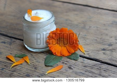 Face cream in a glass jar with a flower calendula on a wooden board.Cosmetics.