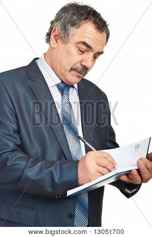 Middle Aged Businessman Writing In Agenda