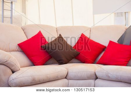 Brown and red pillows on gray sofa