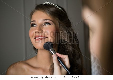 portrait of beautiful glamour woman with blonde curly hair, make up artist finishing make up to bride at wedding morning