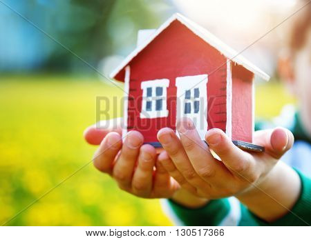 childs hands holding red wooden model house