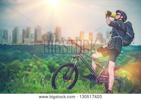 Mountain Biking Near the City. Mountain Biker Refreshing His Body By Drinking Fresh Cold Water.