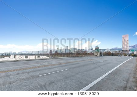 concrete road near water with cityscape and skyline of portland
