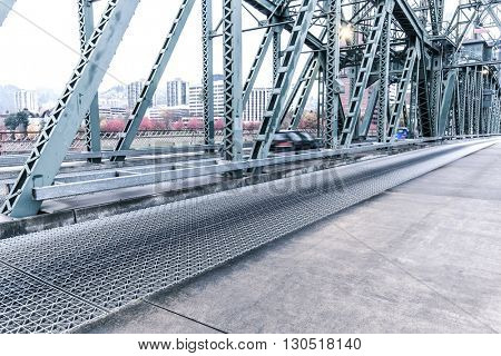 empty pedestrian walkway near road on steel bridge