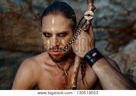 Tribal warrior. Young attractive man outdoor portrait.