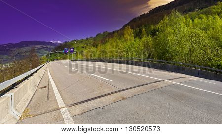 Asphalt Road on the Background of Snow-capped Alps in Switzerland at Sunset