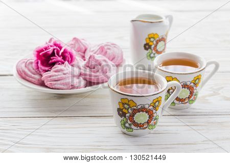 Homemade marshmallow dessert with carnations and two cups of tea