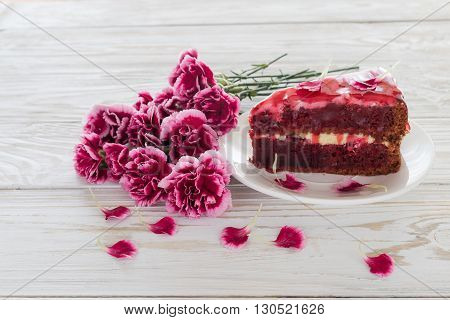 Red velvet cake and pink carnations on wooden table