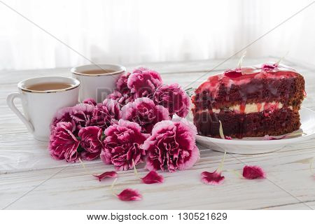 Red velvet cake, two cups of tea and pink carnations on wooden table